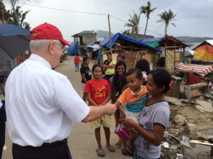 Archbishop greets a mother and child in the Philippines.